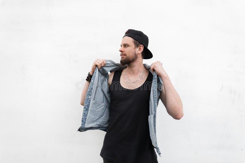 Den attraktiva unga hipsteren som mannen i stilfull grov bomullstvill tilldelar den svarta t-skjortan i moderiktigt lock, poserar royaltyfria bilder