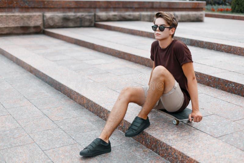 Den attraktiva unga hipstermannen i mörk solglasögon i trendig kläder för sommar i gymnastikskor sitter på en skateboard i staden royaltyfri fotografi