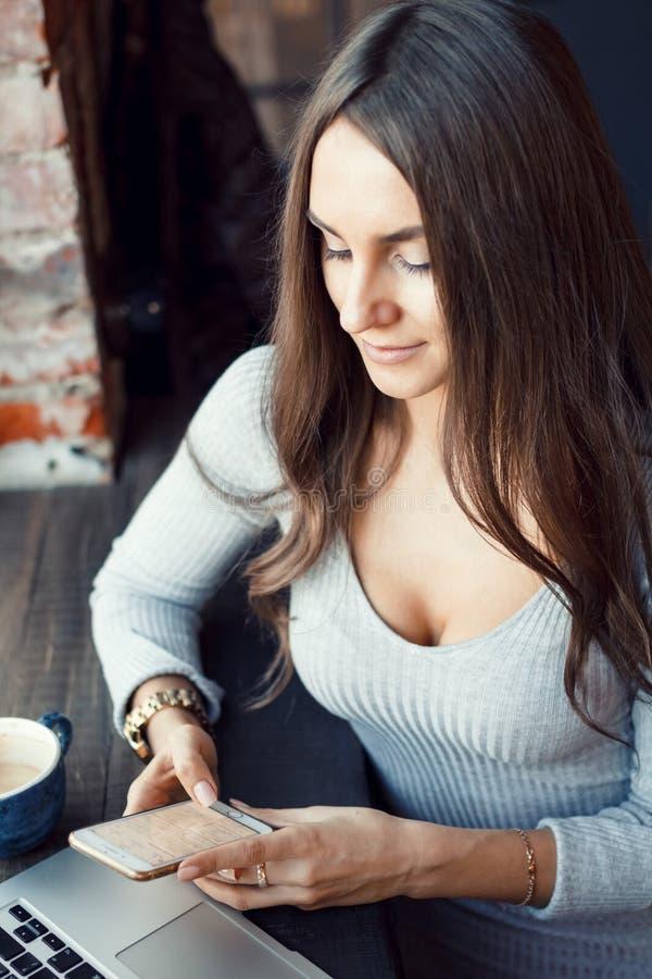 Den attraktiva unga kvinnan använder en mobiltelefon i ett kafé fotografering för bildbyråer
