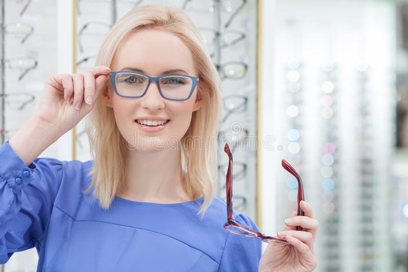 Den attraktiva unga kvinnan bär anblickar shoppar in fotografering för bildbyråer
