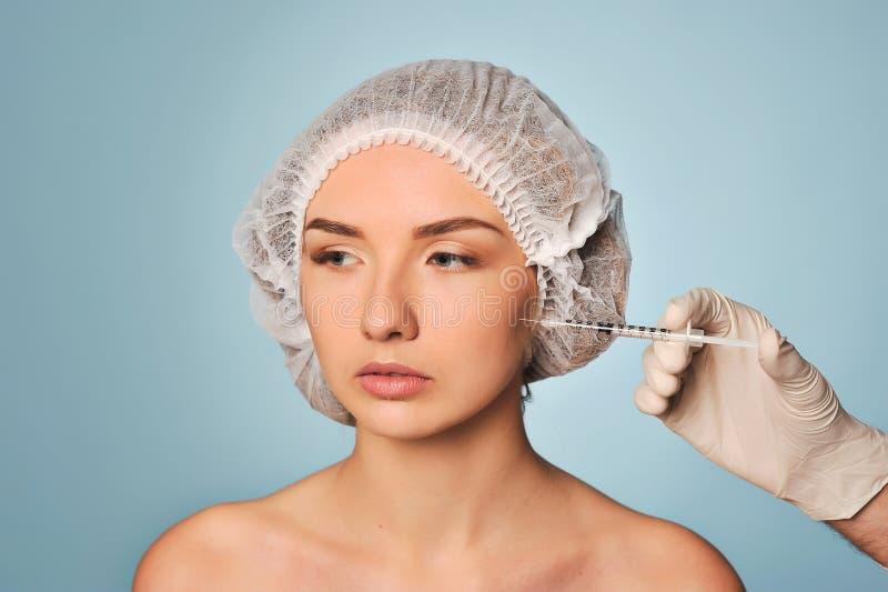 Den attraktiva unga kvinnan får den kosmetiska injektionen arkivfoto