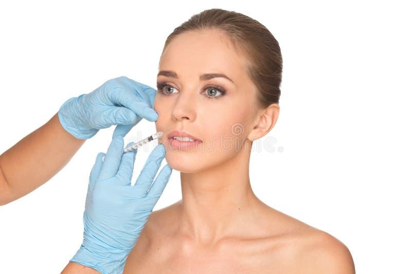 Den attraktiva unga kvinnan får den kosmetiska injektionen av botox fotografering för bildbyråer