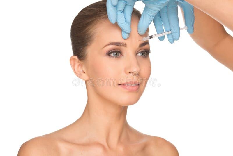 Den attraktiva unga kvinnan får den kosmetiska injektionen av botox royaltyfria bilder