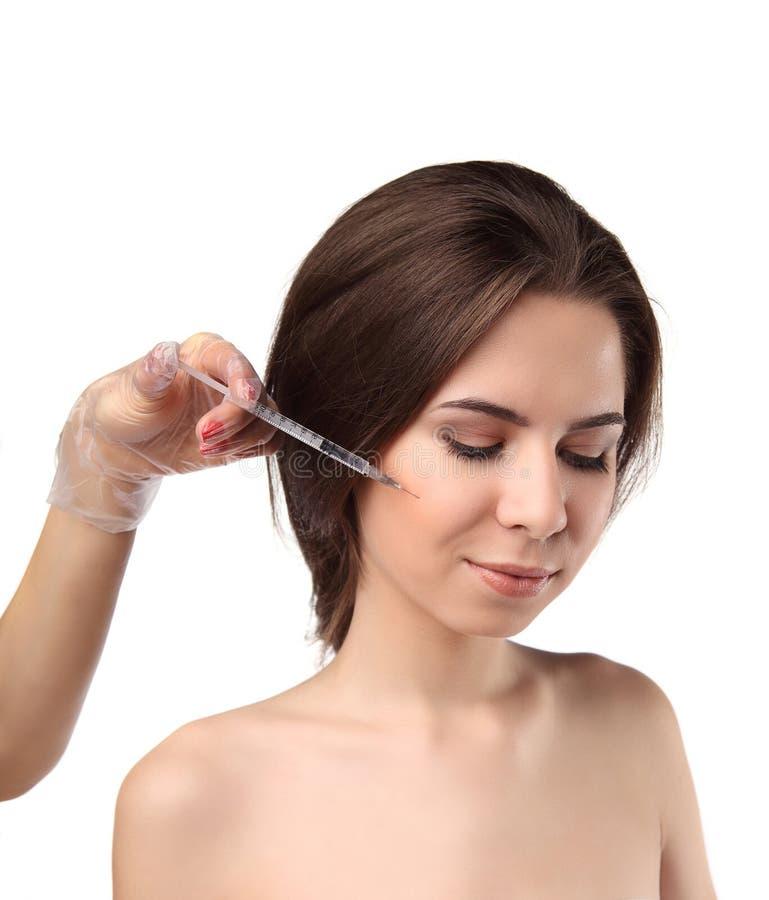 Den attraktiva unga kvinnan får den kosmetiska injektionen med stängda ögon som isoleras över vit bakgrund Doktorshänder som gör  royaltyfri bild