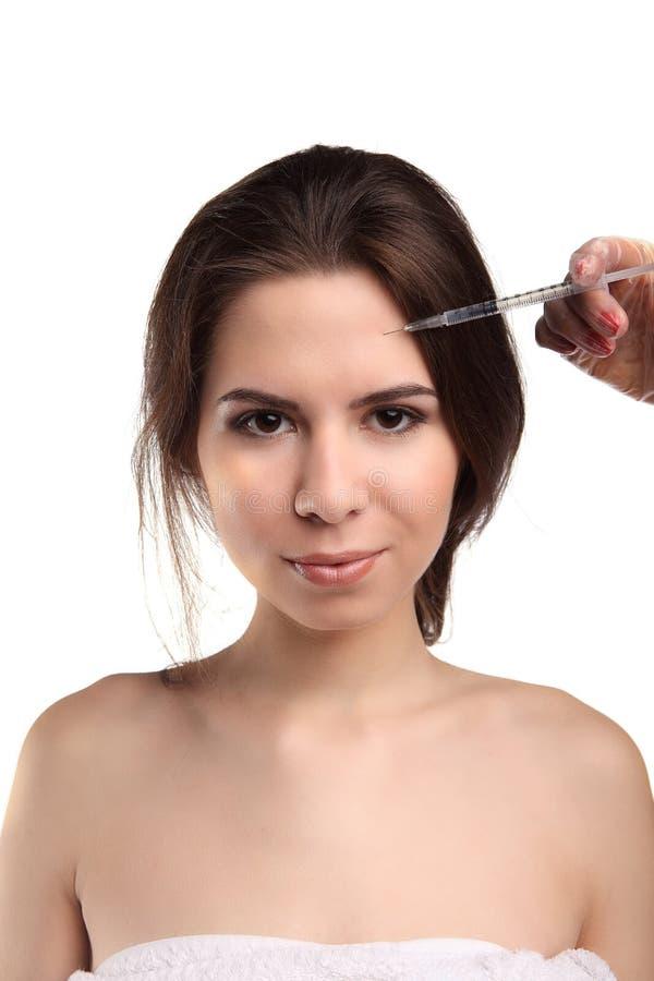 Den attraktiva unga kvinnan får den kosmetiska injektionen som isoleras över vit bakgrund Doktorshänder som gör en injektion i fr royaltyfria bilder