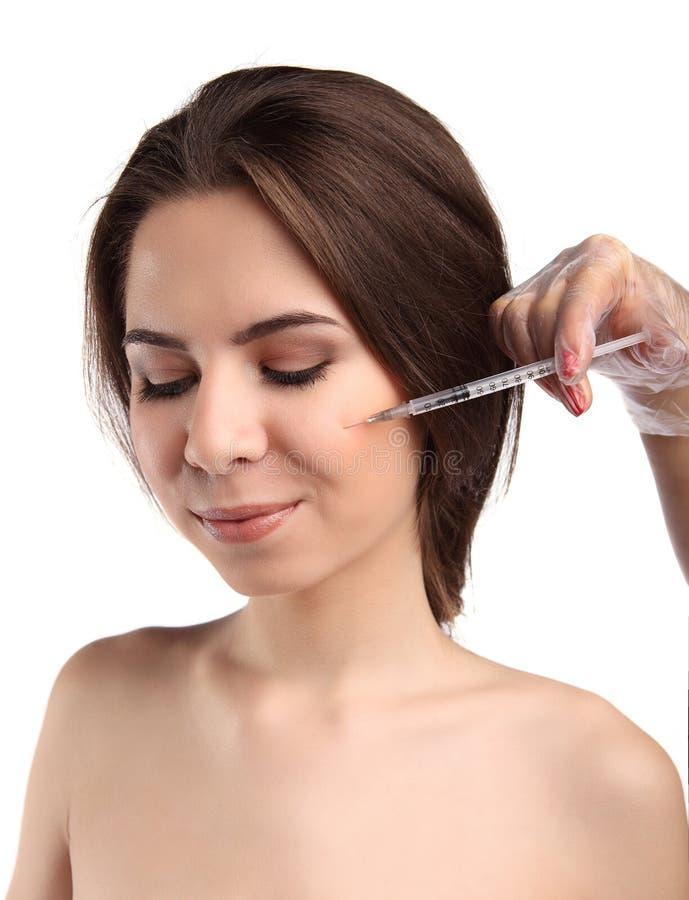 Den attraktiva unga kvinnan får den kosmetiska injektionen som isoleras över vit bakgrund Stängda ögon, makeup royaltyfria bilder