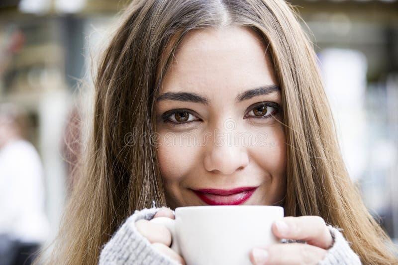 Den attraktiva unga kvinnan har ett kaffe på en gata med bakgrund för gataliv i hösttid royaltyfri foto