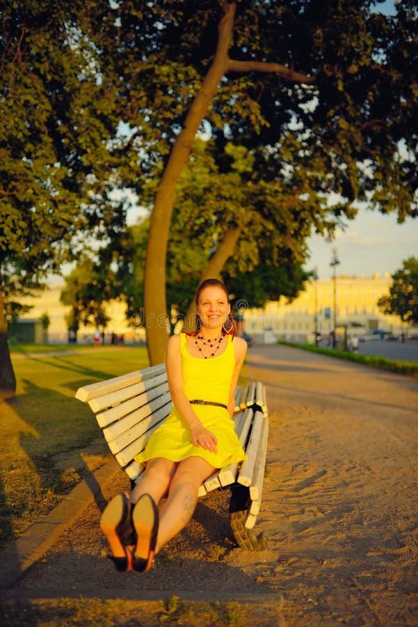 Den attraktiva unga kvinnan i den gula klänningen som sitter i en sommar, parkerar på en bänk arkivbild