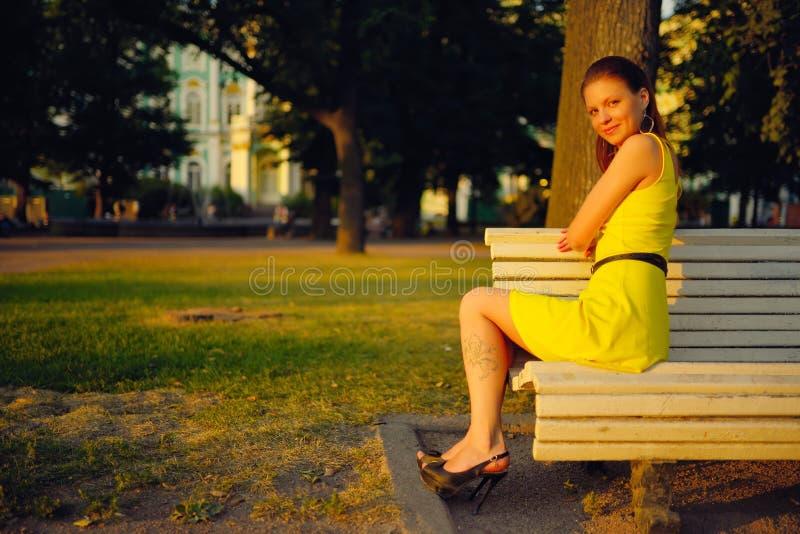 Den attraktiva unga kvinnan i den gula klänningen som sitter i en sommar, parkerar på en bänk royaltyfri bild