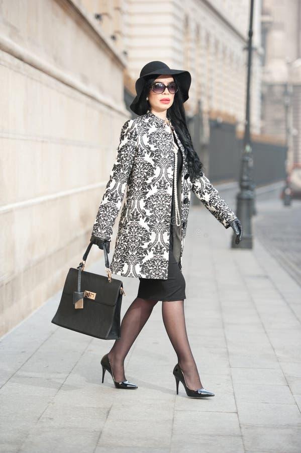 Den attraktiva unga kvinnan i en vinter danar skjutit Härlig trendig ung flicka i svart som poserar på aveny Elegant brunett arkivbild