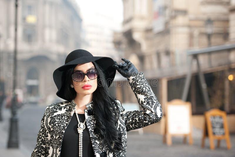 Den attraktiva unga kvinnan i en vinter danar skjutit Härlig trendig ung flicka i svart som poserar på aveny Elegant brunett arkivbilder