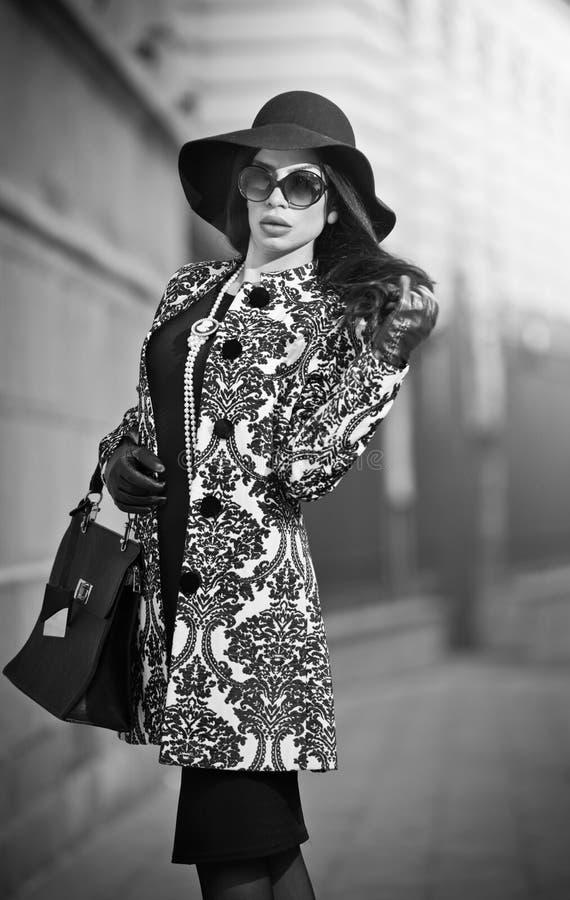 Den attraktiva unga kvinnan i en vinter danar skjutit Härlig trendig ung flicka i svart som poserar på aveny Elegant brunett royaltyfria bilder