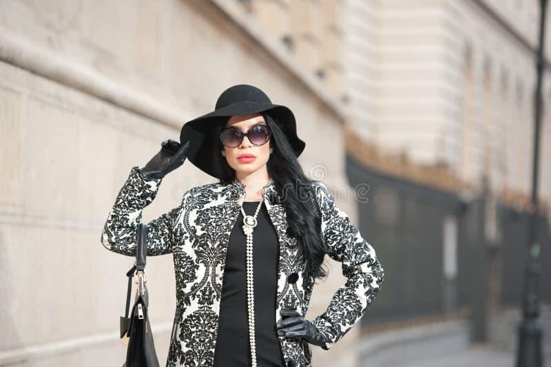 Den attraktiva unga kvinnan i en vinter danar skjutit Härlig trendig ung flicka i svart som poserar på aveny Elegant brunett arkivfoto