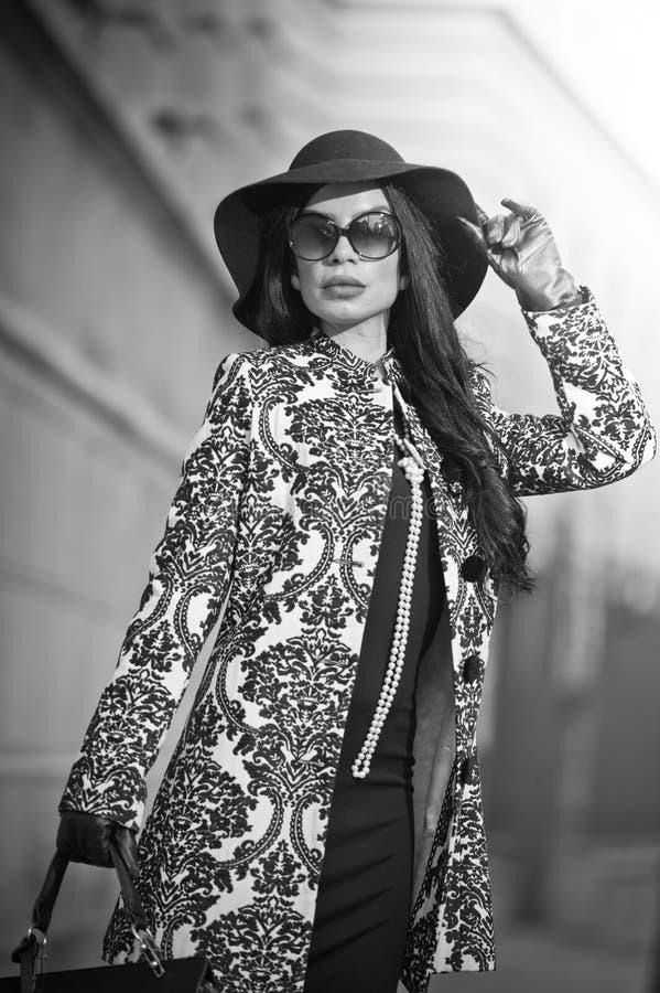 Den attraktiva unga kvinnan i en vinter danar skjutit Härlig trendig ung flicka i svart som poserar på aveny Elegant brunett royaltyfri bild