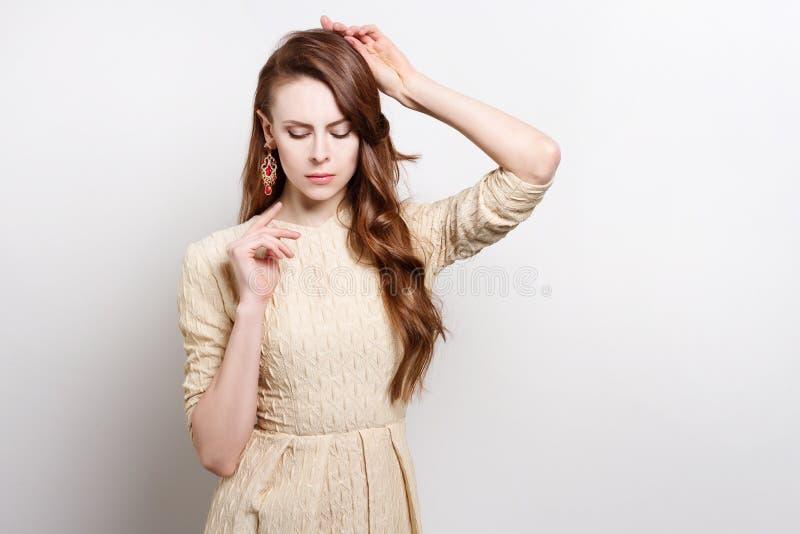Den attraktiva unga kvinnan i guld- klänning är att stå som lyfter hans händer till hans framsida royaltyfri fotografi