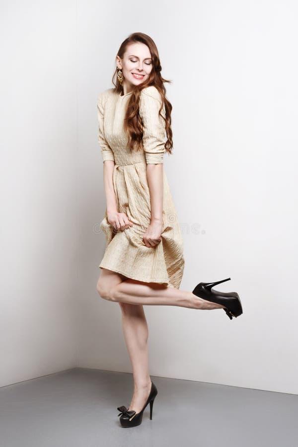 Den attraktiva unga kvinnan i guld- klänning ler, och ställningar i mode poserar royaltyfri fotografi