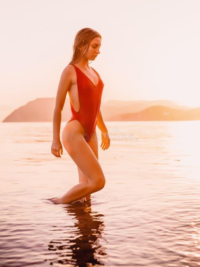 Den attraktiva unga kvinnan i röd swimwearbikini som kopplar av på stranden med varm solnedgång, färgar royaltyfria foton