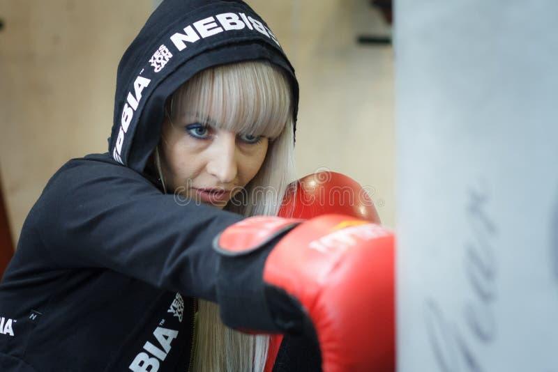 Den attraktiva unga kvinnan i röda boxas handskar står i en boxare poserar klart för strid royaltyfria foton