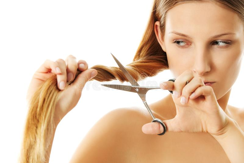 Den attraktiva unga kvinnan klipper hennes långa naturliga hår arkivfoto