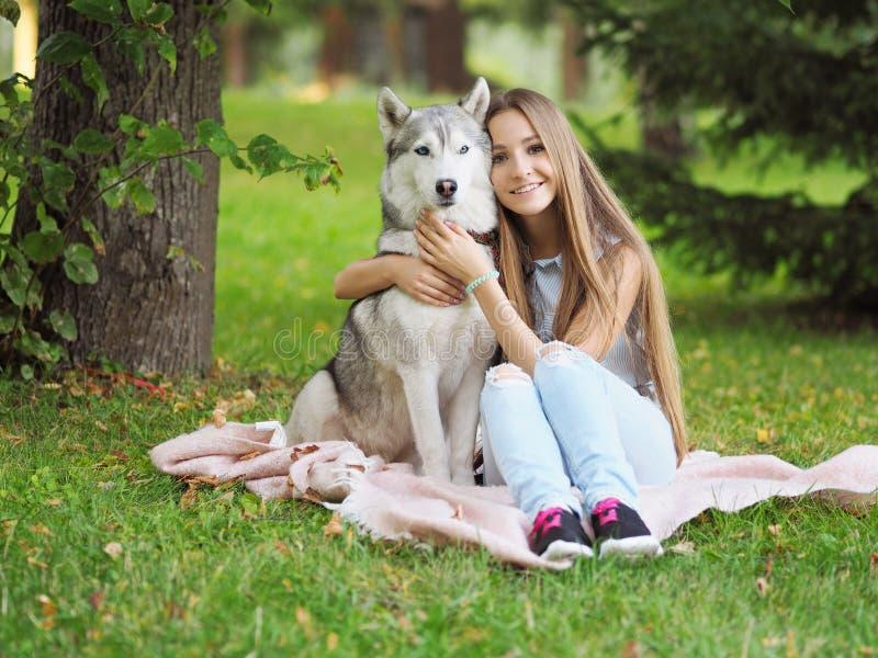 Den attraktiva unga kvinnan kramar den roliga siberian skrovliga hunden arkivbild