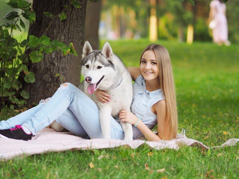 Den attraktiva unga kvinnan kramar den roliga siberian skrovliga hunden arkivfoton