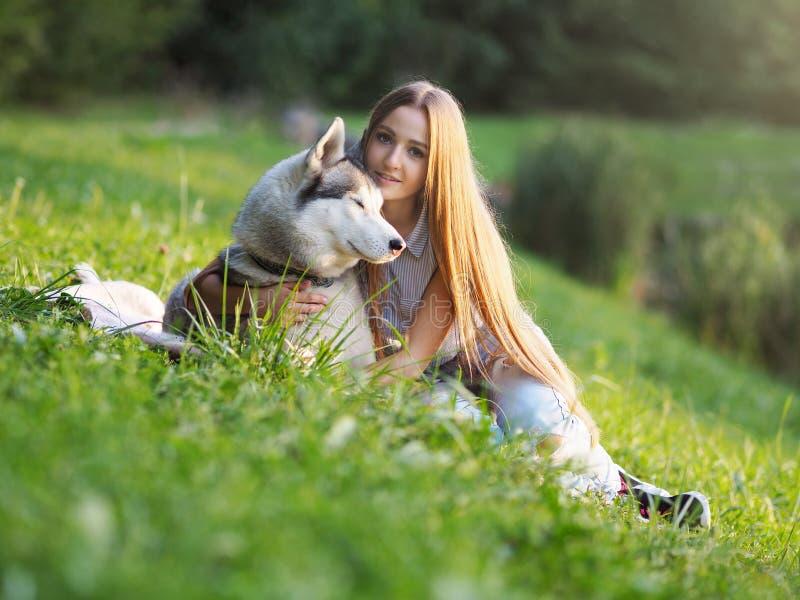 Den attraktiva unga kvinnan kramar den roliga siberian skrovliga hunden royaltyfri fotografi