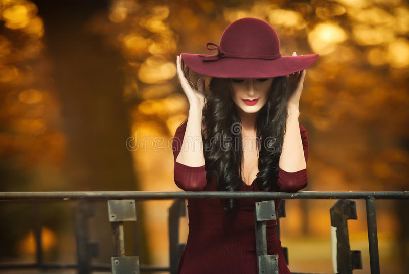 Den attraktiva unga kvinnan med burgundy färgade den stora hatten i höstligt modeskott Härlig mystisk dam som täcker framsidan fotografering för bildbyråer