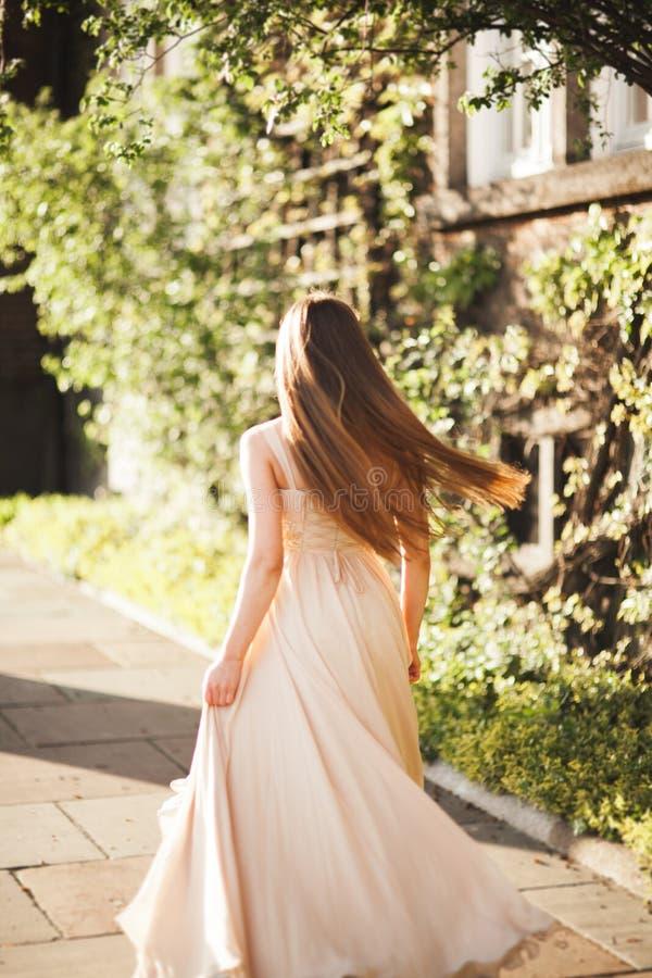Den attraktiva unga kvinnan med den långa klänningen som tycker om hennes tid utanför i, parkerar solnedgångbakgrund royaltyfria foton