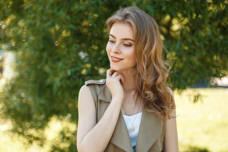 Den attraktiva unga kvinnan med ett härligt leende i en trendig sommar tilldelar en vit T-tröja som utomhus poserar royaltyfri fotografi