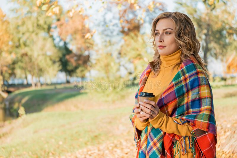 Den attraktiva unga kvinnan med lockigt hår som slås in, i varm filt och att gå i höst, parkerar yttersidan med koppen kaffe arkivbilder