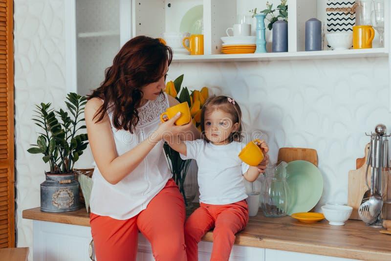 Den attraktiva unga kvinnan och hennes lilla gulliga dotter lagar mat p? k?k royaltyfria foton