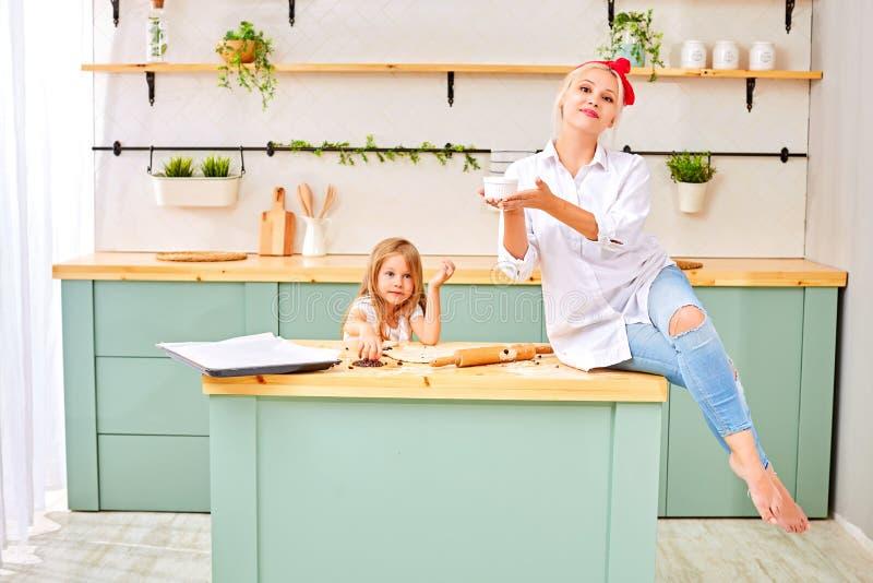 Den attraktiva unga kvinnan och hennes lilla gulliga dotter lagar mat p? k?k royaltyfri fotografi