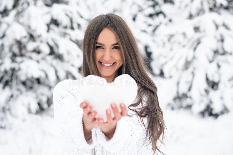 Den attraktiva unga kvinnan rymmer en hjärta från det insnöat vintern royaltyfri bild