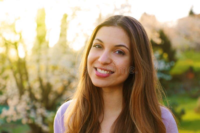 Den attraktiva unga kvinnan som tycker om hennes tid utanför i, parkerar med solnedgång i bakgrund arkivfoto