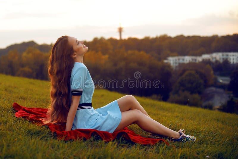 Den attraktiva unga kvinnan som tycker om hennes tid utanför i solnedgång, parkerar Modellera flickan med storartat långt posera  royaltyfri bild