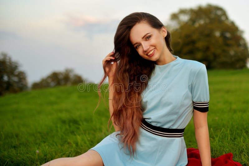 Den attraktiva unga kvinnan som tycker om hennes tid utanför i solnedgång, parkerar Modellera flickan med storartat långt posera  royaltyfria foton