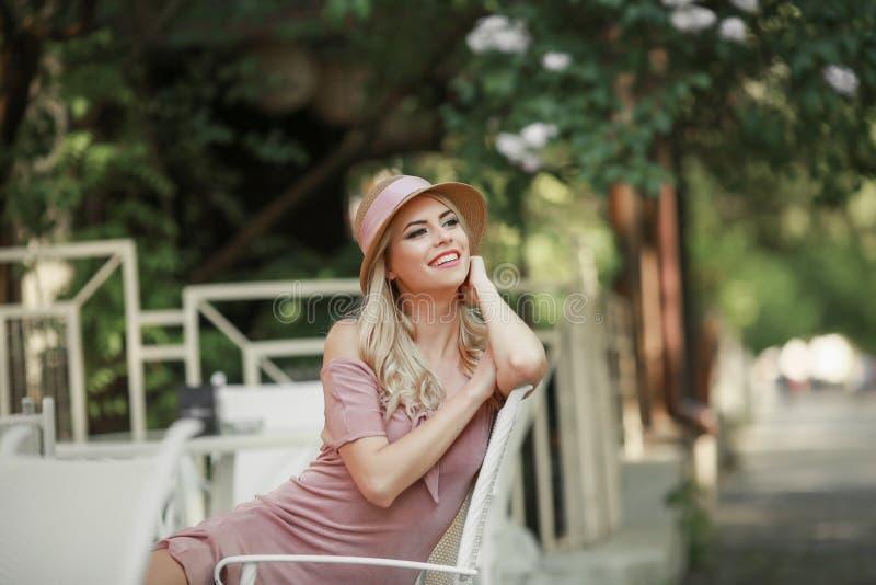 Den attraktiva unga kvinnan som tycker om hennes tid utanf?r i, parkerar med solnedg?ng i bakgrund arkivfoton