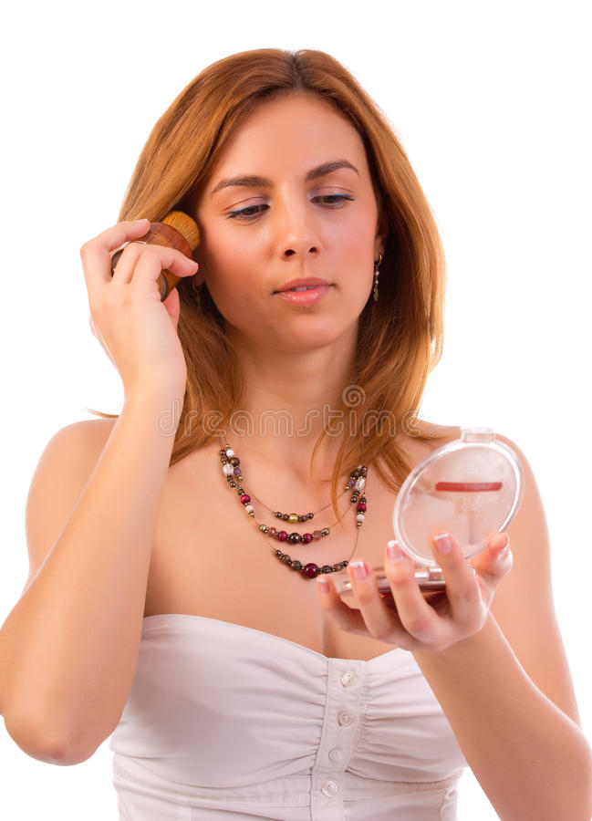 Nätt kvinna som applicerar makeup arkivbilder