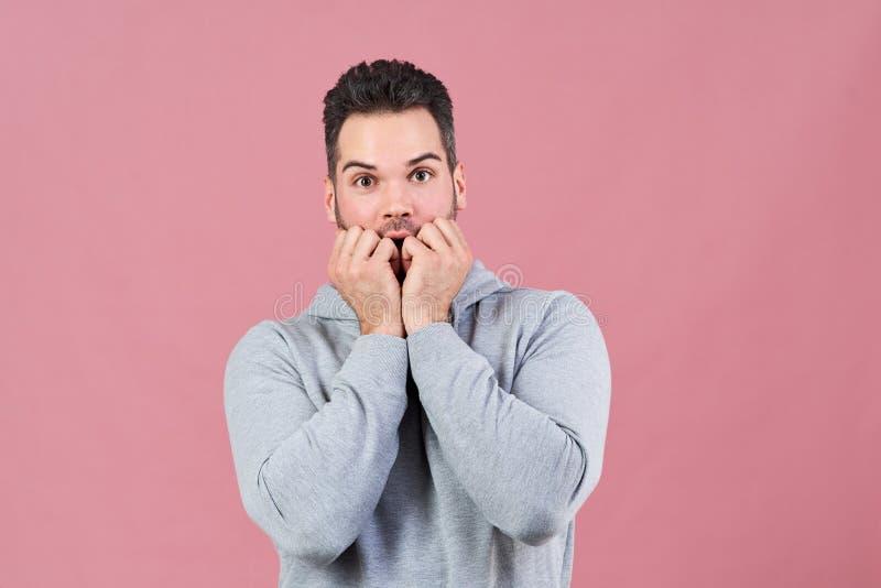 Den attraktiva unga mannen i gråa hoodieblickar skrämde i kameran och trycker på hans nävar till hans mun i ett tecken av skräck  royaltyfria foton