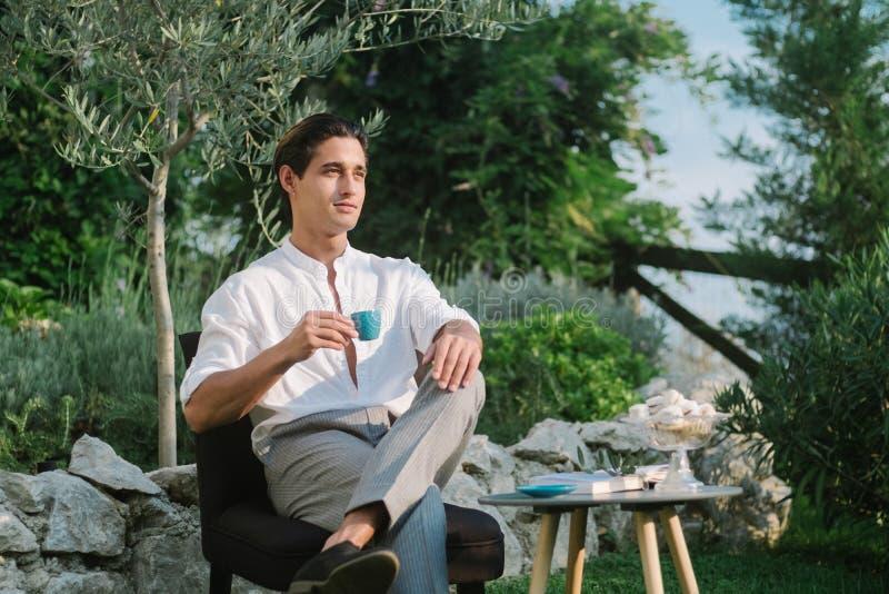 Den attraktiva unga modemannen i en dräkt dricker kaffe i morgonen och läser det fria för en bok i trädgården fotografering för bildbyråer