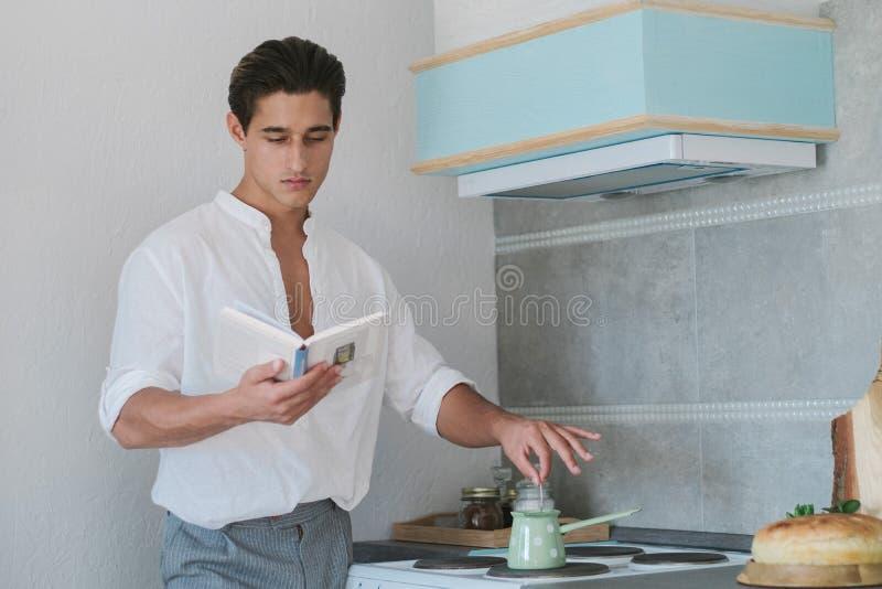 Den attraktiva unga modemannen i en dräkt förbereder turkiskt kaffe och läser en bok i köket arkivbild
