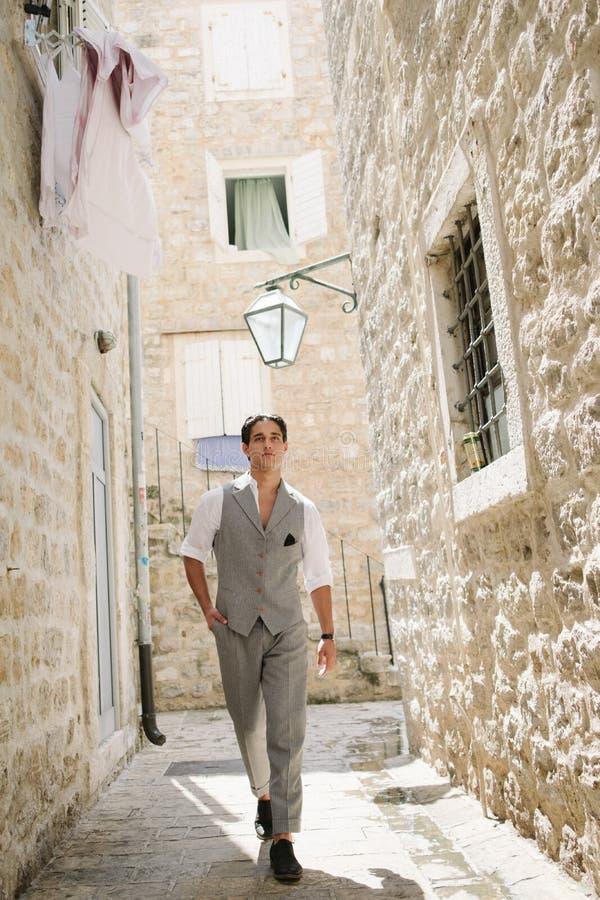 Den attraktiva unga modemannen i en dräkt går runt om den gamla staden royaltyfri bild