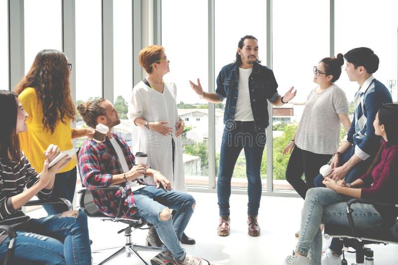 Den attraktiva unga multietniska gruppen som talar på, kopplar av zon i tid för kaffeavbrott på kontoret Ung asiatisk hipsterman  arkivfoton