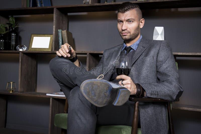 Den attraktiva unga stiliga stilfulla mannen i dräkt sitter i stol med exponeringsglas av rött vin Trendig elegant man i lyxig in royaltyfri bild