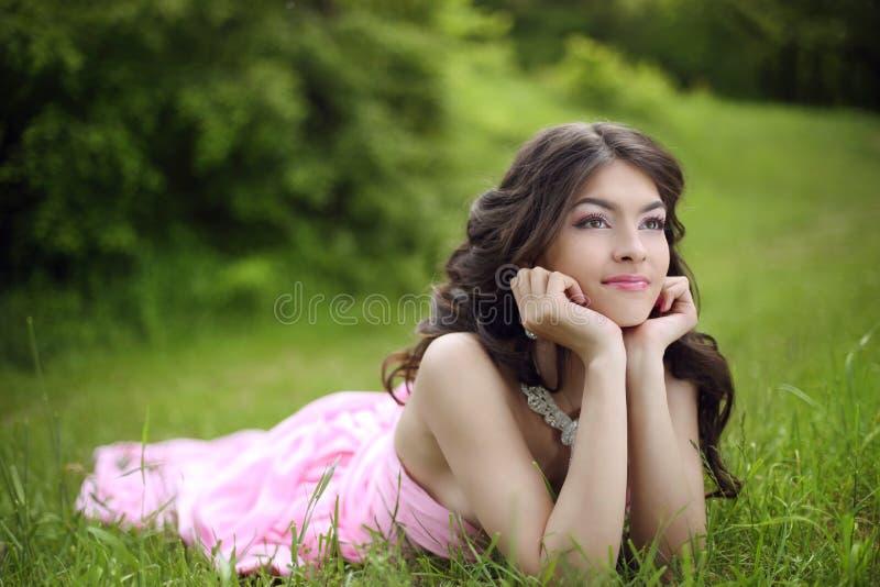 Den attraktiva unga tonåriga flickan med makeup som bär i rosa färger, klär lyi arkivfoton