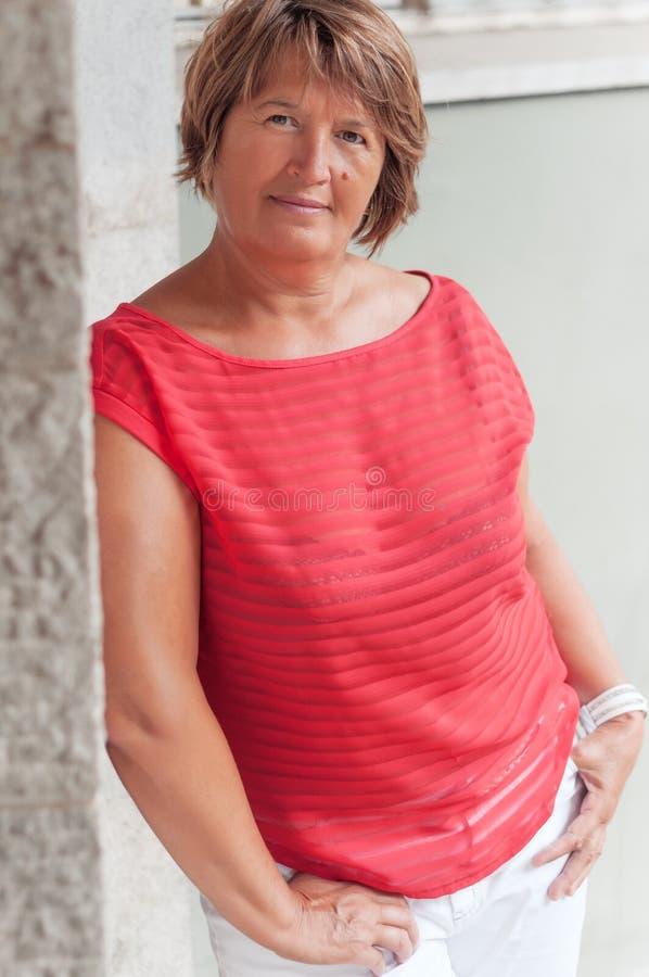 Den attraktiva vuxna kvinnan i röd blus och vit flåsar mot arkivfoton