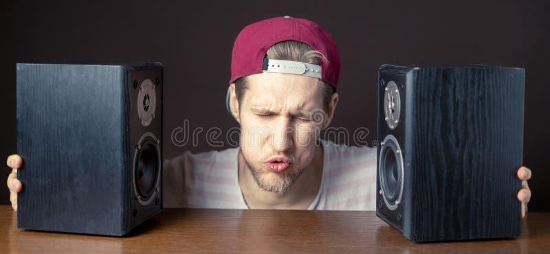 Den audiophile unga mannen lyssnar till hög musik från högtalare f royaltyfri bild