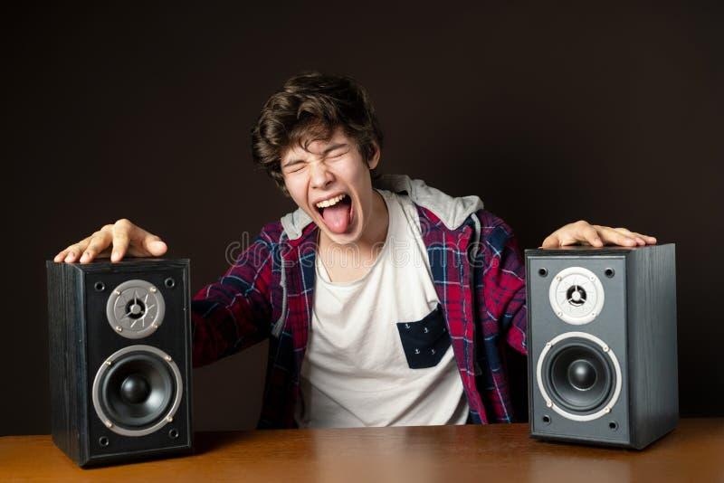 Den audiophile unga mannen lyssnar till hög musik från högtalare f royaltyfria foton
