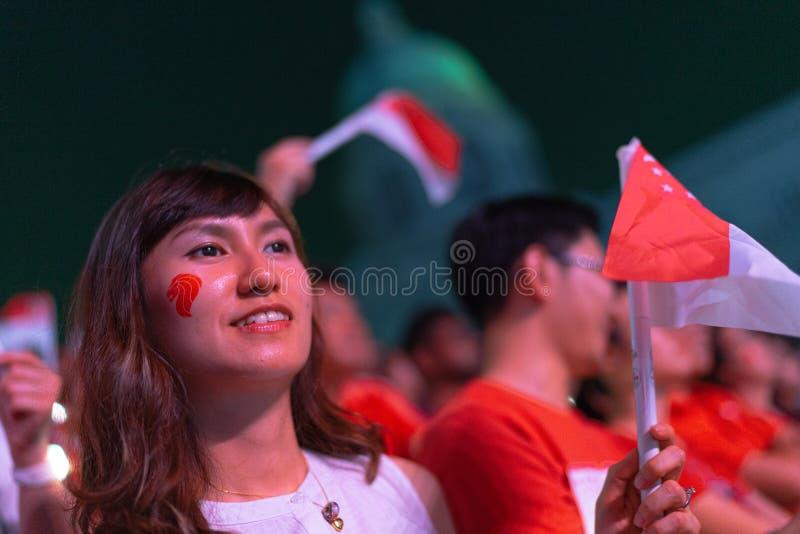 Den 9 augusti 2019 hade den vackra kvinnliga publiken singaporflaggan under Singapores 54:e nationaldag. arkivfoton