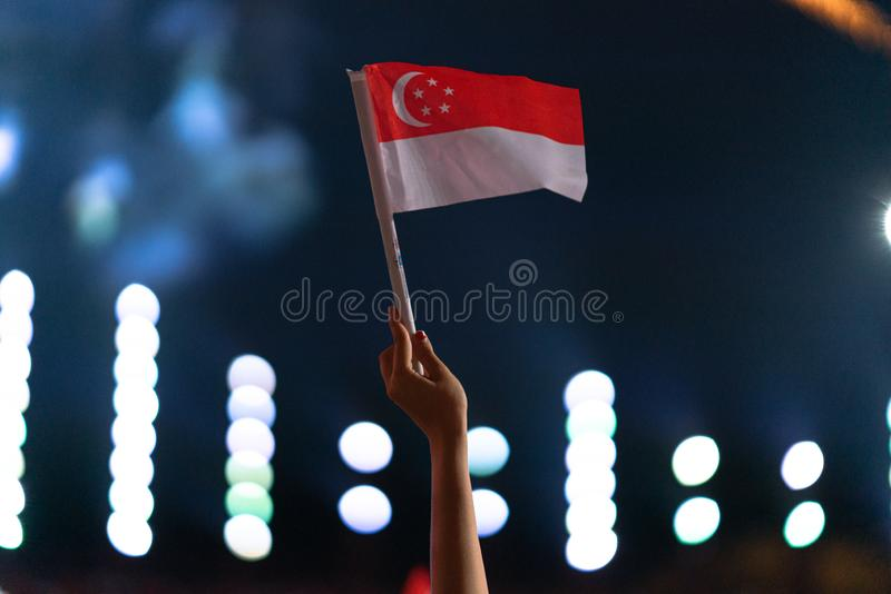 Den 9 augusti 2019 viftade Hand med singapore-flagga under Singapores 54:e nationaldag-parad royaltyfri foto